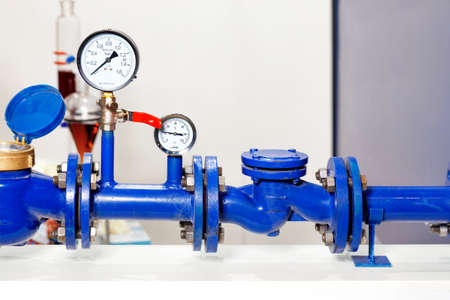 An example of the installation of a metering system and water pressure, close-up of pressure gauges, pipes and taps, copy space.