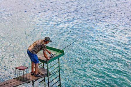 A fisherman in blue denim shorts is catching a spinning rod on the river bank on a summer morning, standing on a wooden platform against the backdrop of clean transparent water, copy space.