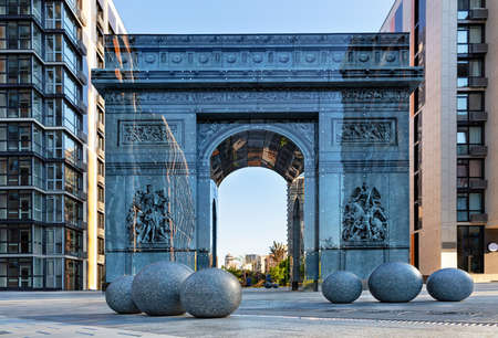 Kyiv, Ukraine, a modern stylized triumphal arch reminiscent of the famous Arc de Triomphe in Paris, located in the French quarter of Kyiv. Stone granite balls in the foreground, drawing on the glass facade.