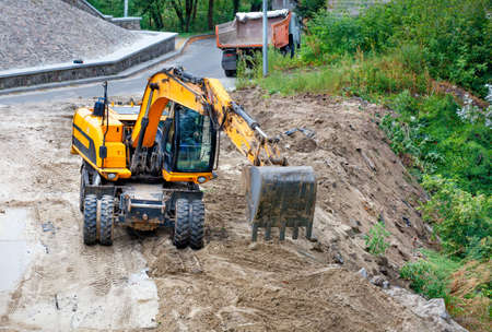 A heavy construction excavator with its bucket levels the sand and backfills the ravine to widen and strengthen the roadway, image with a copy of the space.