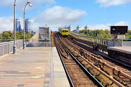 An open section of the railway track of a metro bridge in Kyiv, along which a lemon-colored subway train rushes against a backdrop of a cityscape and a blue sky. Foreground in a slight blur for copy space. 免版税图像