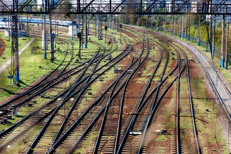 An extensive multi-channel rail network for trains, diagonal perspective and rhythm, top view through the fence mesh.
