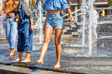 Beautiful figure and legs of a young girl walking barefoot among the high jets of the city fountain and refreshing water on a hot summer day.