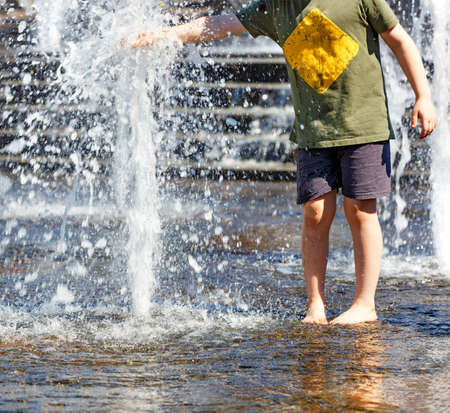 A teenager walks barefoot by the city fountain and tries to grab a powerful stream of water with his hand on a hot summer day. Standard-Bild