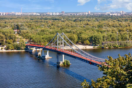 Pedestrian bridge over the Dnipro river to the beach of Trukhaniv island at noon in Kyiv, aerial view, Ukraine.