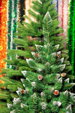 Artificial Christmas pine tree with opened cones and white tassels on the branches against a background of multicolored tinsel in blur. 免版税图像