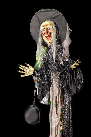 Halloween, death doll in a black hat, rags and a black bag on a metal chain on his arm.