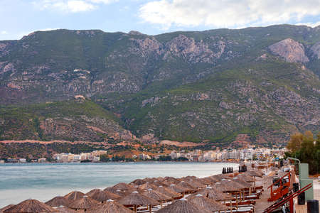 Thatched peaks of beach umbrellas with sun loungers on the deserted shore of the Corinthian Gulf embankment against the backdrop of the morning colors of the awakening city of Loutraki in Greece and mountain ranges in haze and blur.