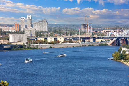 Dnipro river with pleasure boats plying along the city embankment of Kiev on a bright summer day against the background of a beautiful sky and cityscape.