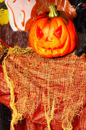 Laughing pumpkin Halloween Jack-o-lantern like ghost with orange and red dress.