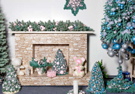New Years holiday, near the stone beige fireplace there are gifts, decorative Christmas trees, toys, balls and spruce branches in green pearl shades, image with copy space.