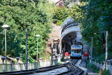 A blue and white cable funicular, surrounded by green foliage and shaded by trees, picks up passengers at the lower station.