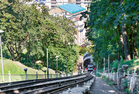 A cable funicular, surrounded by the green foliage of a summer park, picks up passengers at the bottom station to lift them up the mountainside. 免版税图像