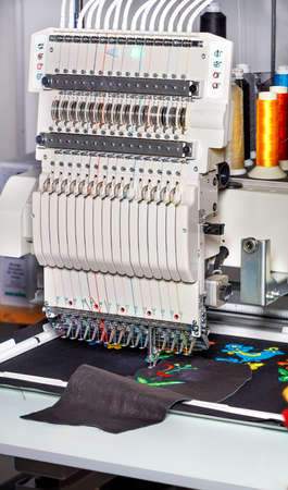 Modern professional embroidery machine for embroidery on various fabrics and leather with multi-colored spools of thread in a blur, vertical image, space for text.