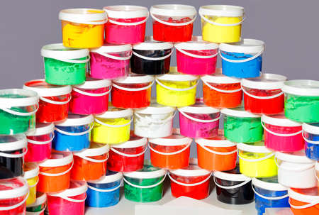 Screen-printing ink in a variety of vibrant colors is laid out in a semicircle and a slide in transparent plastic containers.