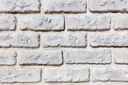 Background and texture of an old brick wall painted white, closeup.