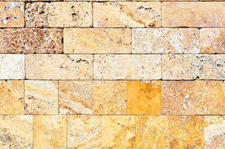 Wall background and texture of hewn yellow seashell stone, close-up.