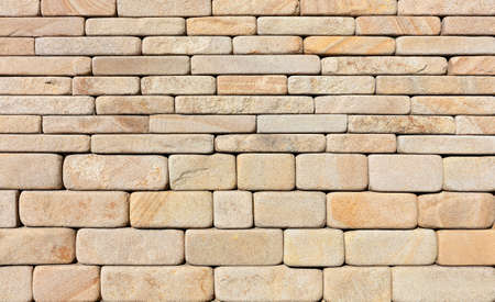 Wall background and texture of hewn rounded yellow sandstone stone, close-up.