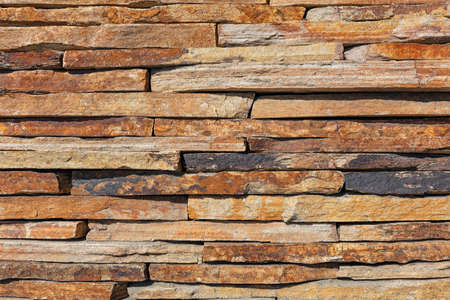 Wall background and texture of brown old slate stone, close-up.