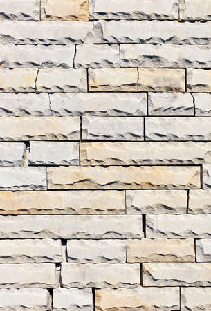 Background and surface texture of tiles of gray and yellow sandstone with chipping and cracks along the perimeter, close-up, vertical image. 免版税图像