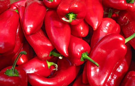 Sweet red ripe peppers on the market counter. A large number of red peppers in a stack, selective focus.