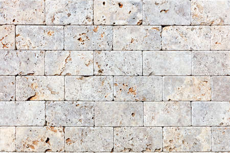 Background and texture of hewn gray shell stone, even rows, neat masonry, close-up.