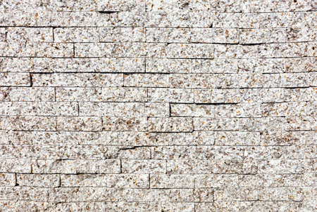Wall background and texture with gray granite stripes with beige spots, close-up.
