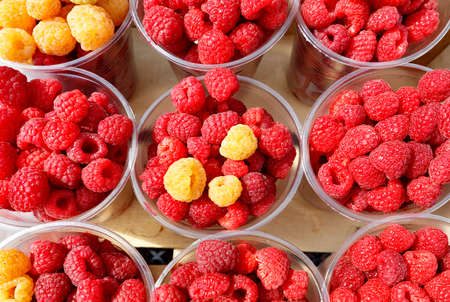 Red and yellow raspberries are collected in plastic cups and sold in street markets, top view.