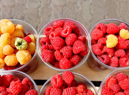 Red and yellow raspberries are collected in plastic cups and sold in street markets, top view, space for text.