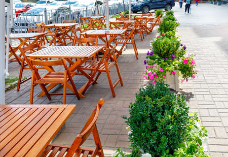 The wooden furniture of the street cafe is deserted against the backdrop of the city sidewalk and part of the road with passing cars.