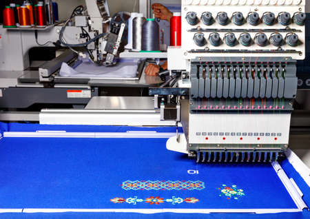 A modern professional embroidery machine for embroidery on various fabrics makes patterns with multi-colored spools of thread, space for text.