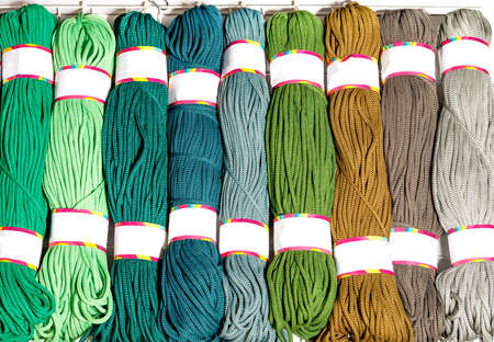 Rolls of polyester cord in various bright colors of green and beige, rolled up, close-up, copy space.