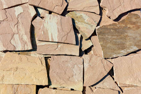 Texture and background of large slabs of brown sandstone in harsh sunlight.