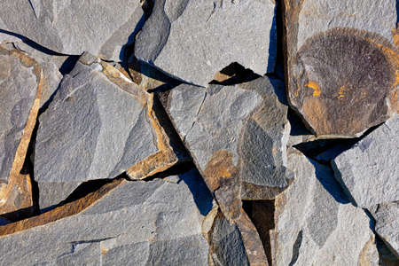 Texture and background of large chunks of rocky gray sandstone with rifts and rusty spots in harsh sunlight.