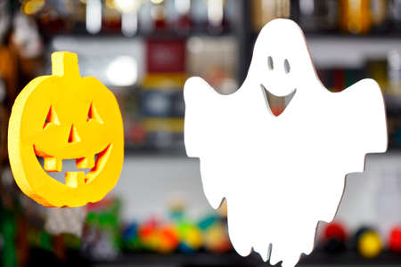 Halloween, two soaring merry ghosts in the form of a pumpkin head and a white ghost on a blurred background.