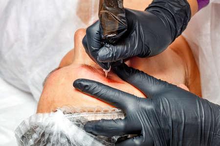 Permanent makeup. Permanent eyebrow tattoo, medical cosmetology. Beautician applies permanent makeup on eyebrows, eyebrow tattoo.