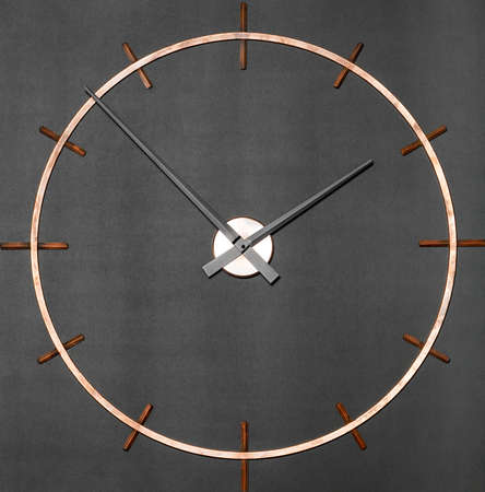 Round industrial wall clock in brass on a granite black background.