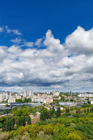 Cityscape of Kyiv in summer at noon with a green park, residential areas and a TV tower against a blue sky with thickening clouds. Bird's-eye view. Copy space.