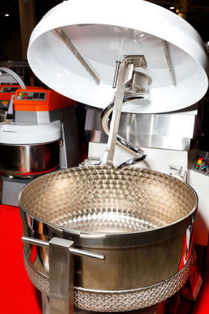 Large kneader made of stainless steel for professional production of dough and various food mixtures, close-up.