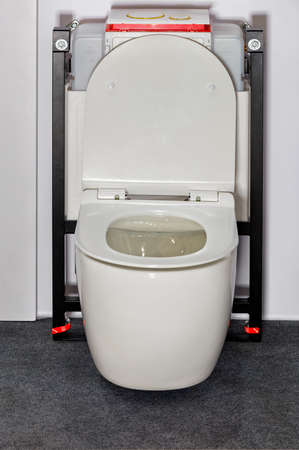 White toilet with a modern concealed wall system and flush mechanism.