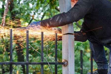A worker cuts a metal post with a disc angle grinder, creating a bright plume of many hot sparks.