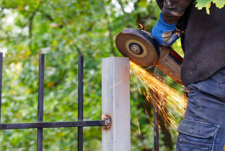 A worker cuts a metal post with a disc angle grinder and sets a fence against a blurred green park, creating a bright plume of many hot sparks.