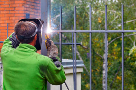 A welder in a protective helmet and gloves using an electrode welds a metal fence in a park area around a residential building, bright sparks, blue smoke fly, selective focus, copy space.