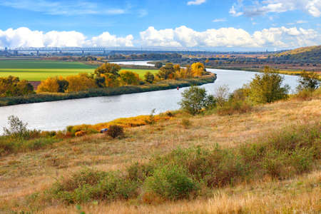 A beautiful autumn landscape with a smooth bend of the river among the plain against the background of a railway bridge on the horizon and a blue sky with white clouds.