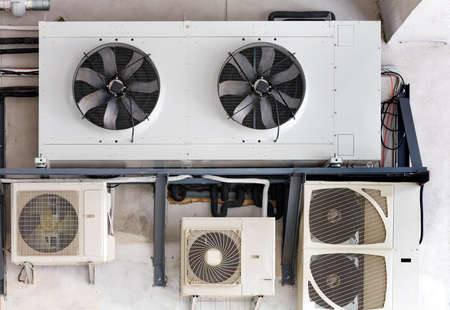 The compressor unit and air conditioners are installed on a metal frame and fixed to the wall of the old building.