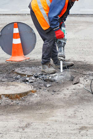 A road worker, dressed in reflective clothing, repairs a section of road near sewers with an electric jackhammer, vertical image, copy space.