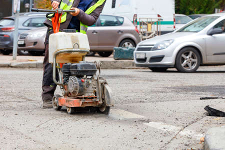 A road worker in reflective clothing cuts old asphalt on the road with a gasoline cutter against the background of a city street in blur. Copy space.