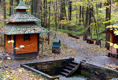 An old wooden Christian baptismal font with spring water hidden in the autumn forest, a wooden building made of rough logs and a plank floor. Stock fotó