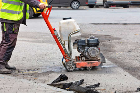 A road worker in reflective overalls uses a portable asphalt cutter to cut worn asphalt with a diamond blade to repair part of the roadway.