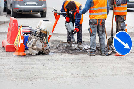 Road workers in reflective clothing on a fenced-in section of road repairing the roadway using a hand-held road tool. Copy space.